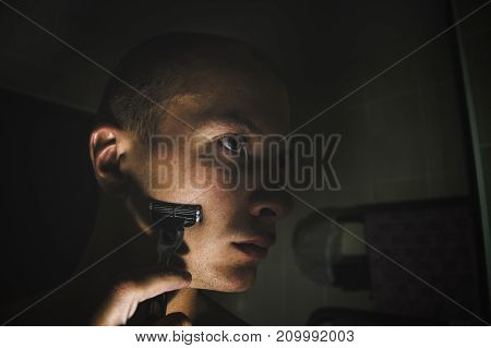 The process of shaving in front of the mirror. Shaving a face with a razor