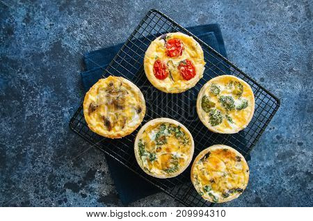 Set of savory mini tarts. Vegetable quiches with tomatoes mushrooms herbs broccoli. Blue stone background.