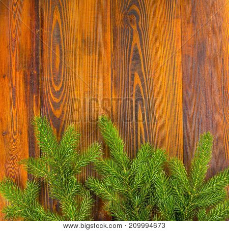 Christmas decoration frame concept background top view on natural rustic wood table surface. Fir tree branches border with copy space