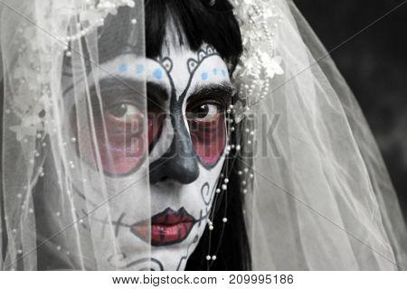 closeup of a bride with a mexican calaveras makeup, wearing diadem and veil