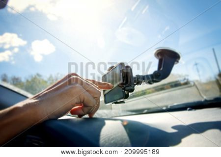 closeup of a young caucasian man using a smartphone as a GPS mounted in a holder stuck in the windscreen of a car