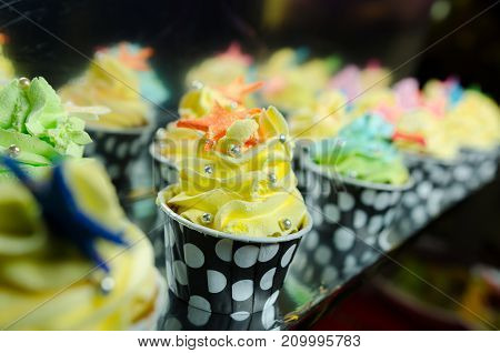 colorful cupcakes frosted with a variety of frosting flavors.