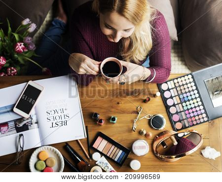 Woman enjoying a coffee break whilst testing make up products