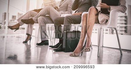 Business people working while waiting in office