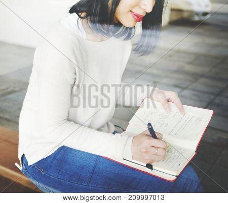 Asian woman writing notes