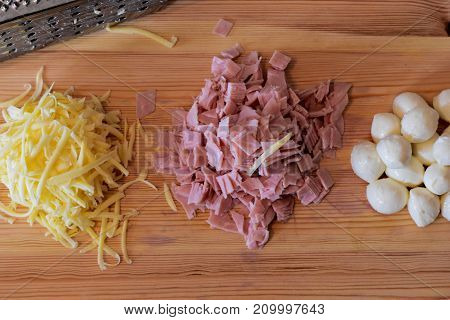 Grated cheese, ham and mozzarella whit metal grater at wooden background/ top view of cooking ingredients