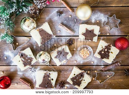 slicesed christmas cake on the background with holidays decorations with cinnamon and stars. top view. cake with a surprise inside