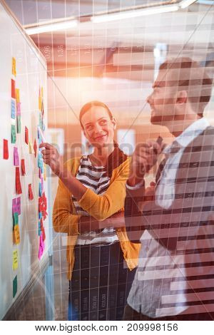 Blue data against female colleague showing sticky notes to businessman