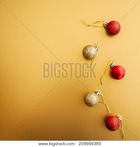 Red Gold Christmas Balls On Golden Background. Selective Focus. Copy Space. Top View. Square Image.