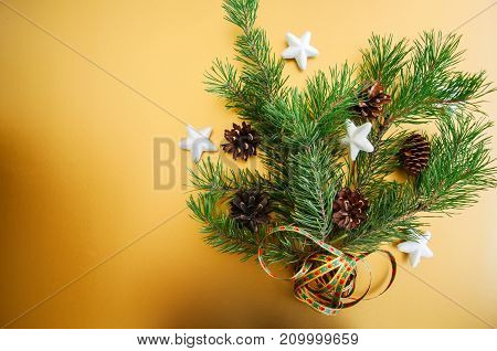 Fir Tree Branches With Cones And Stars Over Golden Background, Festive Decoration.