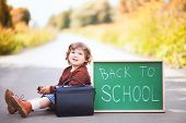 Cute toddler girl wearing school uniform with back to school blackboard wautung gor a school bus. fall outdoors education concept sunny autumn day. early education little genius Wunderkind concept. poster