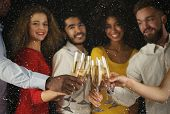 Christmas party time. Young people toasting with champagne flutes. Multiethnic friends congratulating each other with new year. Celebration and nightlife concept, holiday background, selective focus poster