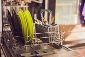 Dishwasher with dirty dishes. Powder dishwashing tablet and rinse aid. Washing dishes in the kitchen. poster