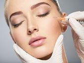 Woman getting cosmetic injection of botox near eyes, closeup. Woman in beauty salon. plastic surgery clinic. poster