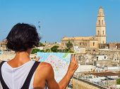 Tourist with a map in his hans in front of Lecce rooftop view with the Campanile bell tower of Cattedrale metropolitana di Santa Maria Assunta cathedral in background. Lecce Puglia Italy. poster