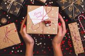 Woman hands holding christmas holiday gift box with postcard merry xmas on decorated festive table with sparkle stars candy cane walnut on wooden background. Packaging gift wrap and ribbons twine. Winter time new year poster