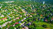 aerial view above Suburb Neighborhood complex growing modern living areas outside of austin texas growing suburbia suburban community green landscape thousands of homes poster