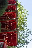 Detail of the tiered eaves of a Japanese pagoda painted brightly in red on a bright summer day. poster