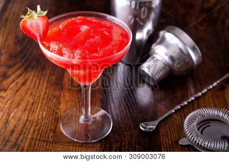 A Delcious Frozen Strawberry Daiquiri On A Wooden Bar Counter Top.