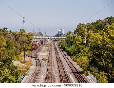 Burlington, Canada - September 23, 2018: Multiple Railway Tracks Head East, With A Freight Train Par
