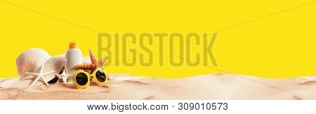 Sunblock Bottle With Summer Accessories On Solid Background