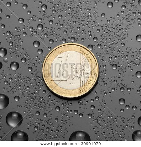 One EURO coin with water drops