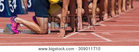 Group Of Male Track Athletes On Starting Blocks.hands On The Starting Line.athletes At The Sprint St