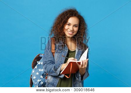 Young African American Girl Teen Student In Denim Clothes, Backpack Hold Books Isolated On Blue Wall