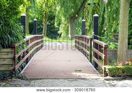Wooden Bridge Over Little River In City Park. Little Arched Wooden Bridge Over Garden Pond. Arched W