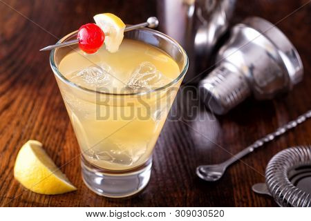 A Delicious Whiskey Sour Cocktail On A Wooden Bar Counter Top.