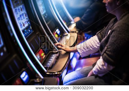 Casino Slot Gamblers. People Playing Video Slot Machines Inside Las Vegas Located Casino.