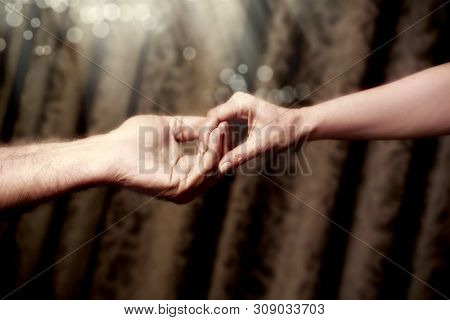 close up senior adult male hand and young adult female hand holding each other
