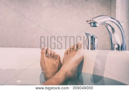 Woman taking a bath at home cozy lifestyle - spa therapy bath salts wellness body care relax girl with feet crossed in happiness.