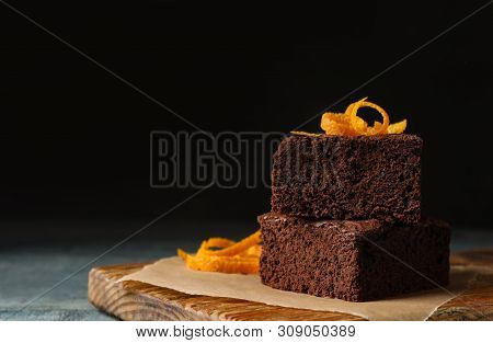 Fresh Brownies Decorated With Orange Peel On Wooden Board, Space For Text. Delicious Chocolate Pie