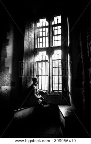 Rear View At Silhouette Of Man Sitting In The Darkness Looking Through Old Bright Window With Incomi