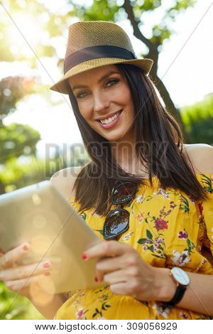 Woman portrait - Happy young woman in the city park outdoor in summer wearing summer dress and trendy hat using tablet computer. Lensflare and vivid colors.