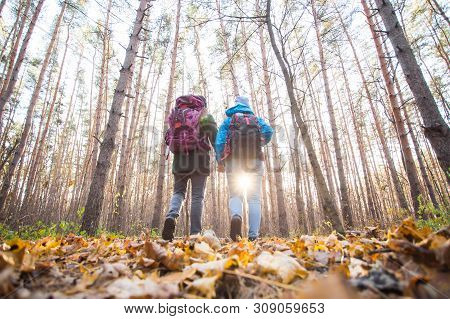 Adventure, Travel, Tourism, Hike And People Concept - Smiling Couple Walking With Backpacks Over Aut