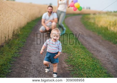 Happy Family Enjoy Weekend In Nature. Loving Parents Watch Their Son Doing First Steps. Baby Learnin
