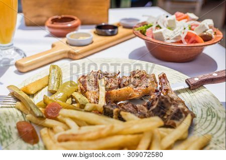 Lamb Chops With Vegetables And Roast Potatoes On A Plate In A Greek Restaurant Or Tavern