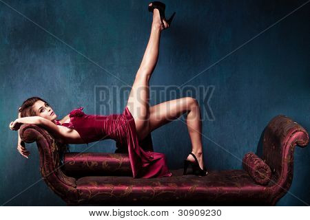 elegant woman in red dress and high heels lie on recliner