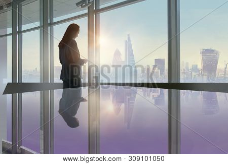 Young Woman Texting On The Phone In Front Of The Big Office Window With City Of London View. Skyscra