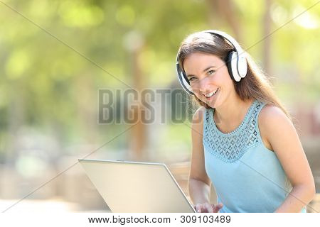 Happy Woman Using A Laptop And Headphones Looks At You In A Park With A Green Background