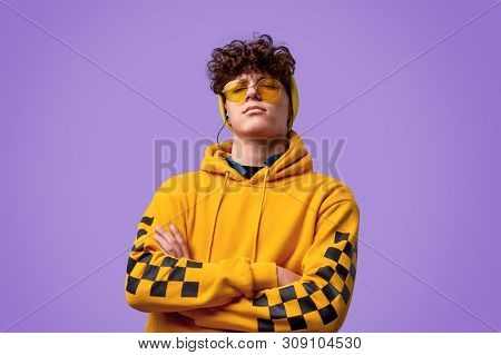 Serious youngster in yellow hoodie and stylish shades crossing arms and looking at camera while standing against purple background poster