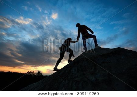 Silhouettes Of Two Climbers Reaching Summit, One Holding Hand Of Partner Assisting To Make Last Step