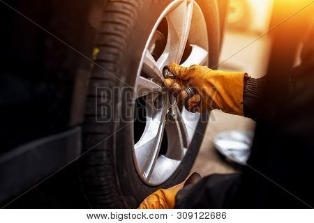 Auto Mechanic Man With Electric Screwdriver Changing Tire Outsid