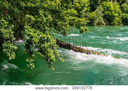 Eautiful View Of The Rhine River In Turquoise, At The Source In Switzerland, Just Behind The Biggest