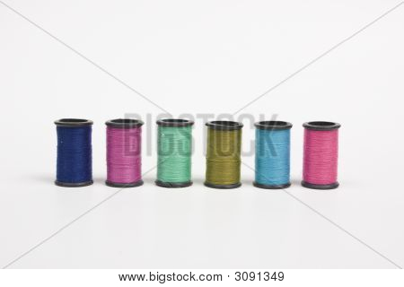 Spools Of Colorful Thread Lined In A Row