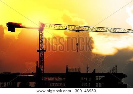 Construction Cranes Working On The Light Of The Setting Sun