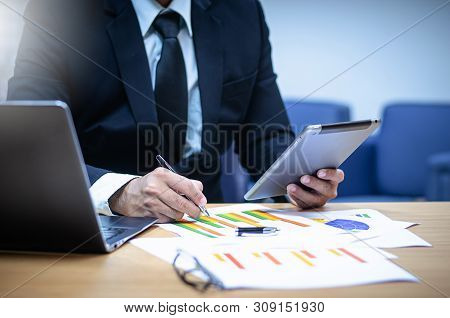 Businessman Sitting With A Laptop In His Office