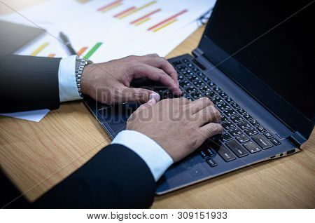 Businessman Stock Market Works On The Laptop Resting On The Desk